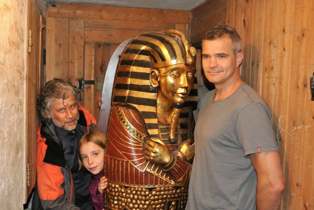 Ram Gupta får Olivia Bettum til å posere inne i mumiekisten mens pappa og egyptolog Anders Bettum presser seg mot veggen. Foto: Arnsten Linstad