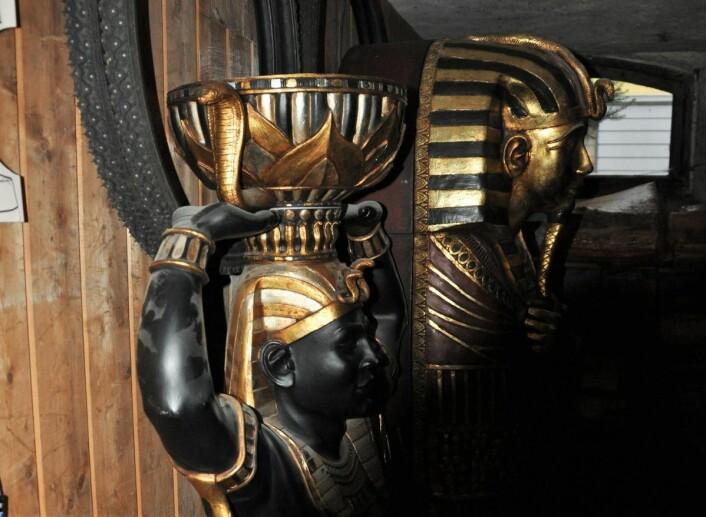 Pent oppstilt i kjellerboden, foran noen sykkeldekk med pigger, står både en nubisk Neferititi-aktig skulptur i ekte plast, og en mumiekiste eller sarkofag i gedigent foreggjort tre med en interessant gjengivelse av Tutankhamons ansikt. Foto: Arnsten Linstad