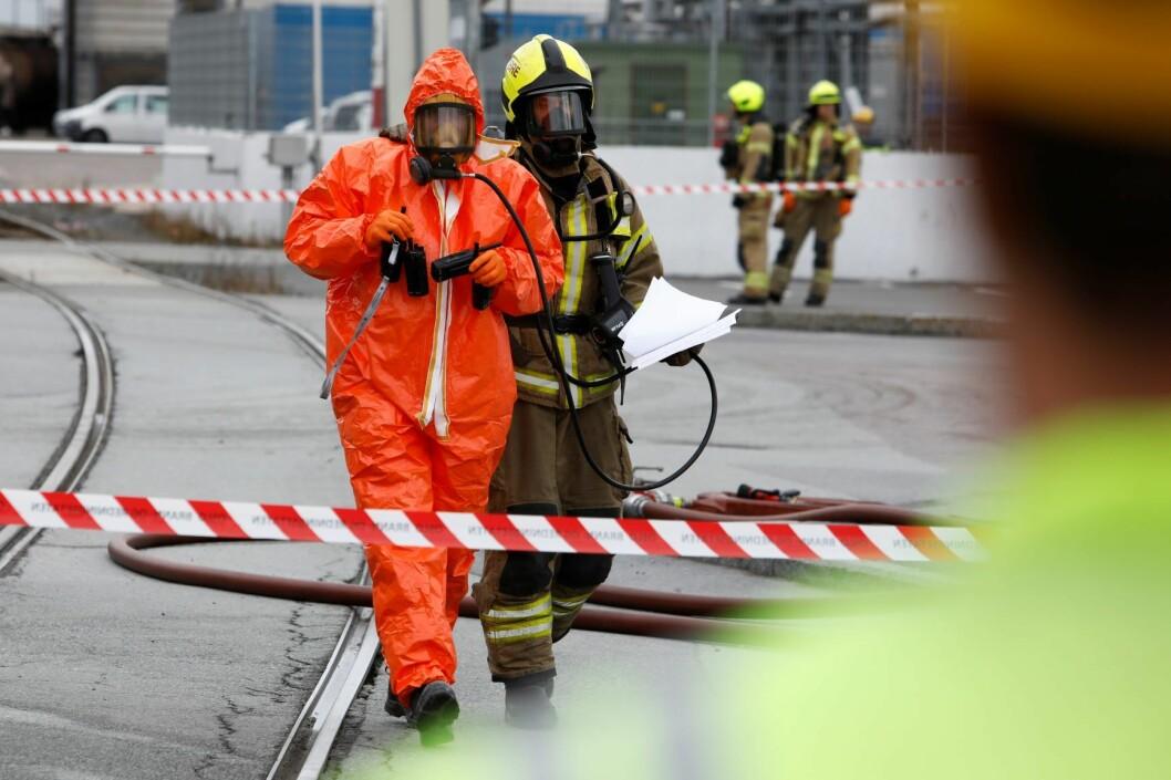 En person blir eskortert ut i oransje drakt etter at det gikk hull i en tank med potensielt giftig innhold på Sjursøya i Oslo. Foto: Tore Meek / NTB scanpix
