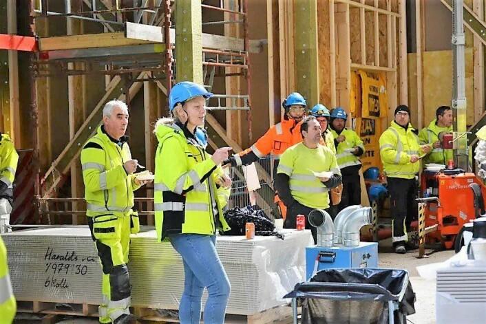 Prosjektleder Pia Sylvie Berg i Undervisningsbygg, i spissen for bygningsarbeiderne, feirer at taket på Hasle skole er tett. Foto: B. Nylund