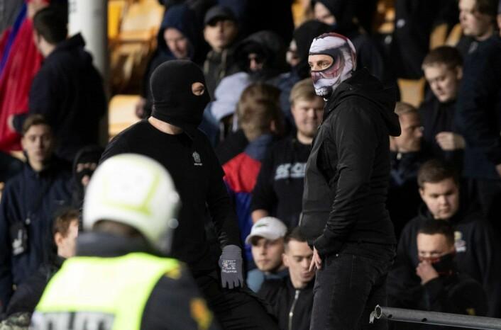 Maskerte menn foran VIFs supportere før bortekampen mot LSK. Nå opplyser politiet på Romerike at flere er identifisert, og at det kan bli flere pågripelser. Foto: Terje Bendiksby / NTB scanpix