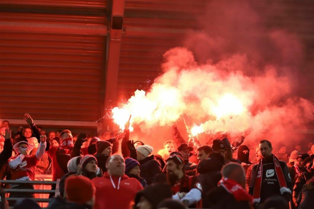 Brann-supportere med bluss på tribunen. Et tosifret antall bluss ble også kastet inn på banen. Foto: André Kjernsli