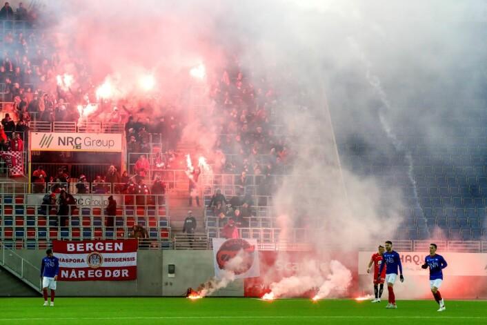 Brannsupportere kaster bluss og fyrverkeri ut på banen under eliteseriekampen i fotball mellom Vålerenga og Brann på Intility Arena Foto: Berit Roald / NTB scanpix