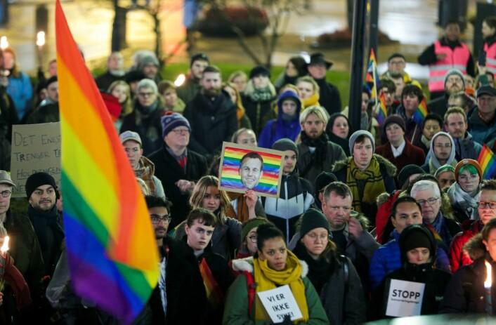 Demonstrantene holdt opp regnbueflagg med bilder av KrF-leder Kjell Ingolf Ropstad på. Foto: Stian Lysberg Solum / NTB scanpix