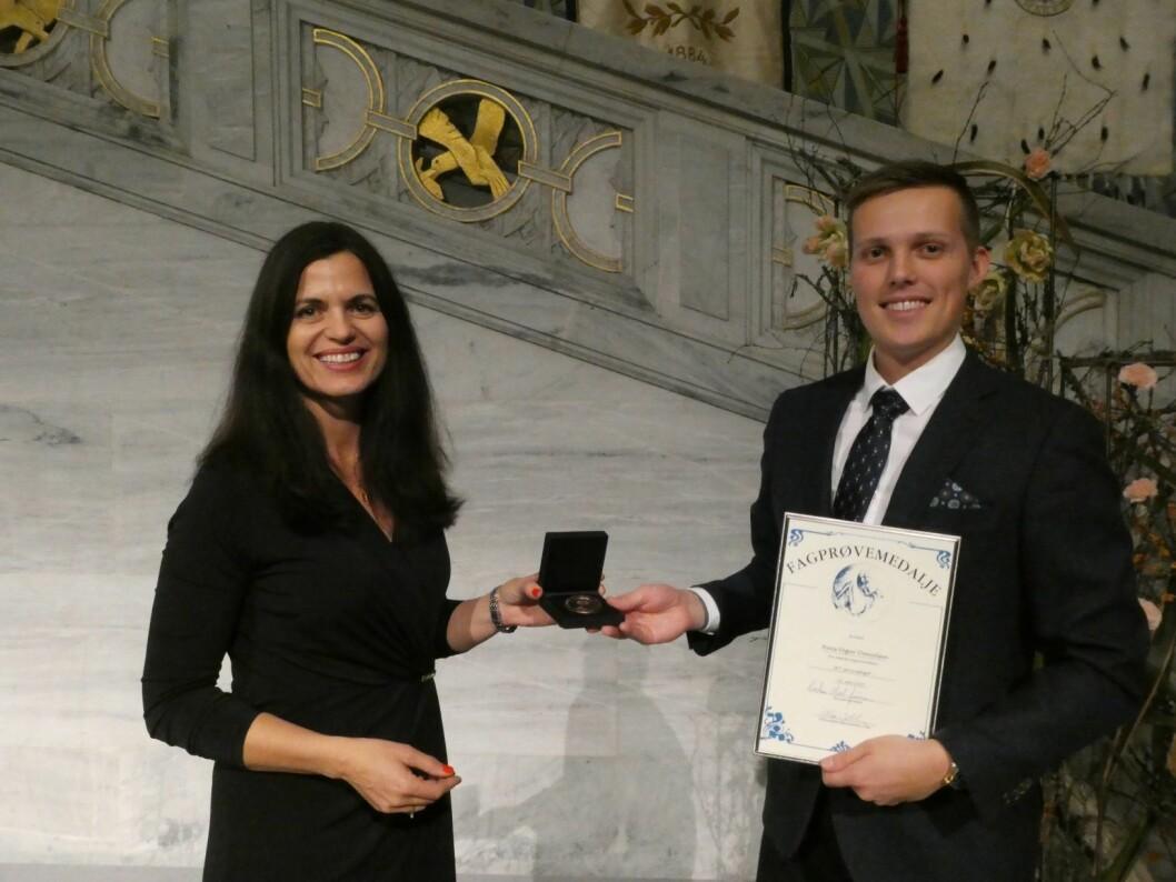 Nina Solli, leder i Yrkesopplæringsnemnda i Oslo, deler ut fagprøvemedaljen for særdeles godt arbeid til Hans Vegar Danielsen. Foto: Ole Kristian Grønneng / Utdanningsetaten