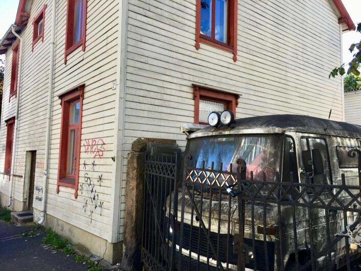 Det høye stålgjerdet til huset er låst igjen med en sykkellås. Foto: Stig Jensen