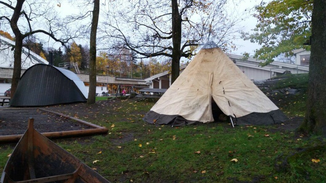 Høstbilde fra Samisk barnehage. Det hvite huset i bakgrunnen er barnehagen. På tunet: lávvu og goahti (tradisjonsbygg), tradisjonell båt og sandkasse. Foto: Mikkel Berg-Nordlie