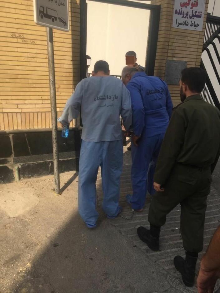 Til venstre i lyseblå fangedrakt går Sorab Abolfathi lenket til en annen fange i Iran. Foto: Privat