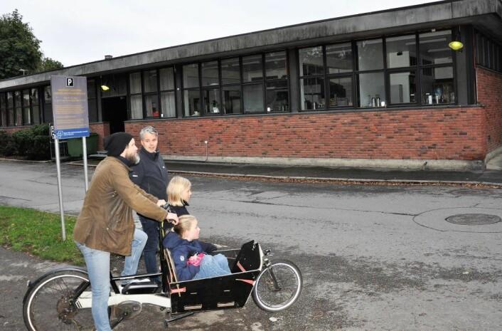 Håvard Lorentzen (på sykkel) med Bolteløkka-elevene Elise og Virva i lasteplanet. Ved siden av står tidligere FAU-leder Magnus Buflod foran velferdsbygget ved Veterinærhøyskolen. Bolteløkka-foreldrene mener bygget kan brukes sammen med paviljongløsningen. Foto: Arnsten Linstad