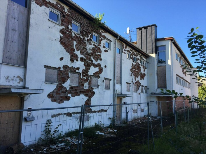 En fasade i svært dårlig forfatning. Unni Hestvedt er fornøyd med at første etasje er stengt igjen med sponplater. Foto: Vegard Velle