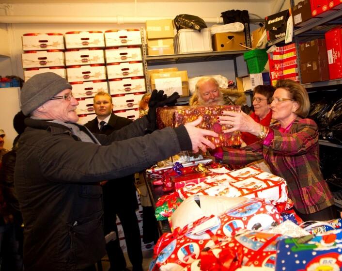 Dronning Sonja er blant dem som har stilt opp for Fattighuset. Her utleverer hun julegaver til en av brukerene. Foto: Morten Holm / SCANPIX
