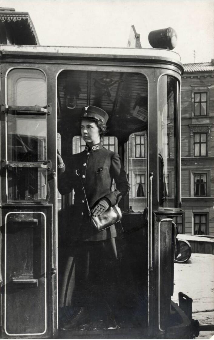 Margit Preede med billettveske mars 1916 da kvinnelige konduktører ble kurset. Bildet er tatt foran<br />Kristiania Sporveisselskabs vognhall i Sporveisgata 8. Gården i bakgrunnen er i Pilestredet. Foto: Johan Markus Holmsen, Oslo Museum