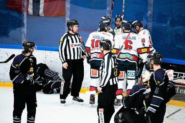 Lillehammer-spillerne jubler for den kontroversielle 4-3-scoringen, mens Robin Olsen Syversen ligger skadet på isen i bakgrunnen Foto: Bjørnar Morønning