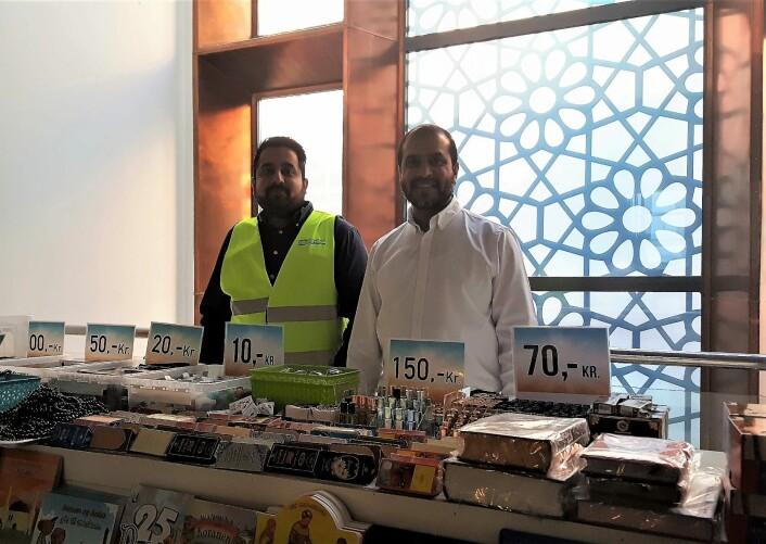 Daglig leder Ikhlaq Bhai i hvit skjorte sammen med Abdul Wahab Shukat viser frem den lille moskebutikken. Dessverre var de denne dagen utsolgt for islamofobi kurerende tyggegummi. Foto: Tarjei Kidd Olsen