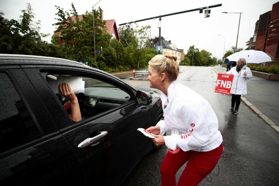 Cecilie Lyngby (FNB) deler ut løpesedler til bilister samme dag som Oslos bomring ble utvidet i fjor sommer. Foto: Lise Åserud / NTB scanpix