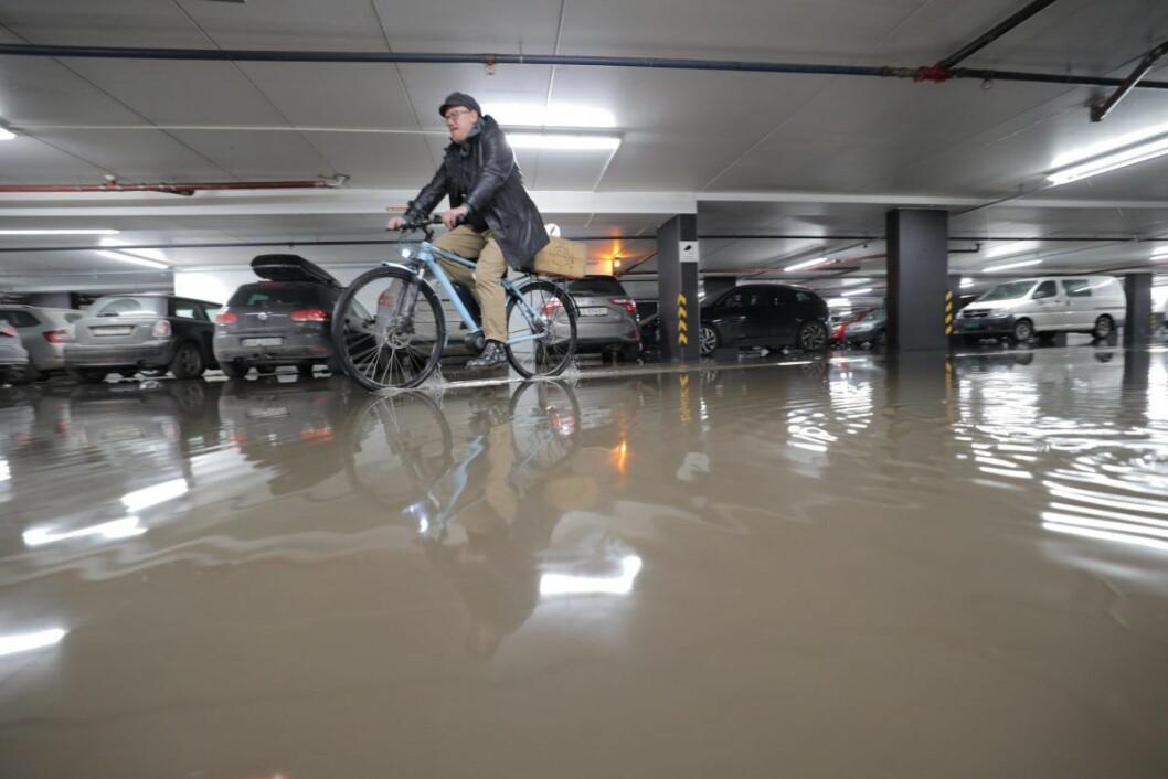 Denne syklisten tok seg elegant gjennom vannet i parkeringshuset i Kiellands hus mandag ettermiddag. Foto: Ørn E. Borgen / NTB scanpix