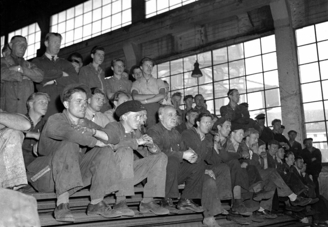 Arbeidere ved Akers Mekaniske verksted, det som i dag er Aker brygge, mens de i 1947 lytter til Filharmonien som spiller i en av verkstedhallene. Foto: NTB / Scanpix
