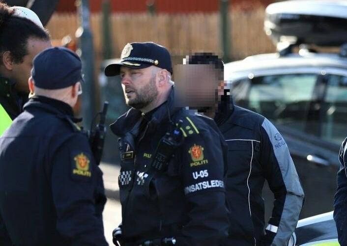 NOKAS-vekter (bak politiets innsatsleder) etter at familiefaren skal ha blitt lagt i bakken og skadet ved å få et kne plassert over halsen slik at han ikke fikk puste. Foto: André Kjernsli