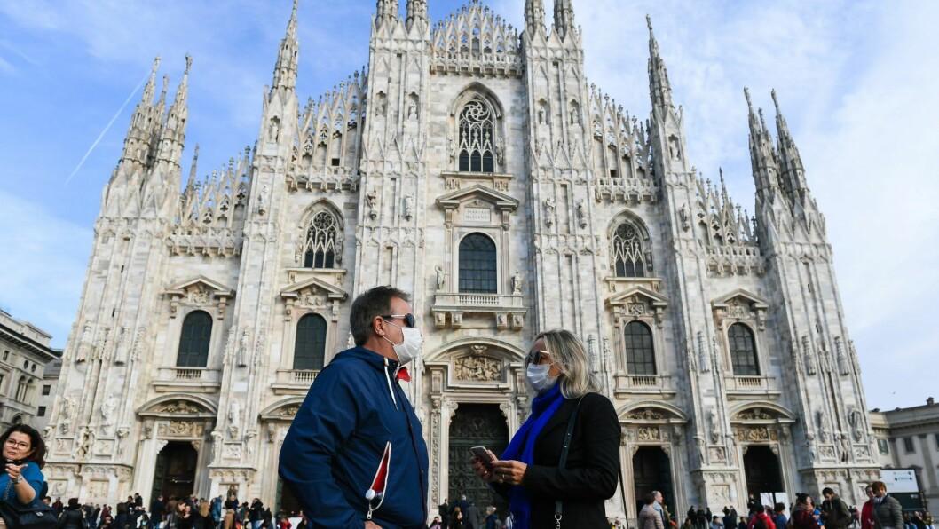 Utenfor Milanos berømte katedral Duomo di Milano går folk med munnbind. Skolene i byen har vært stengt i to uker. Foto: Getty Images