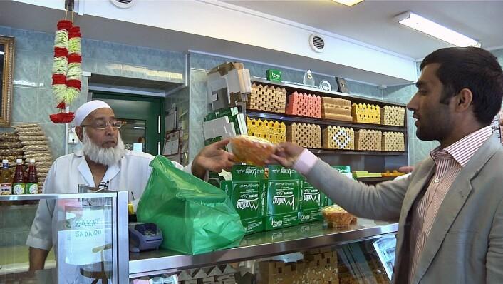 Hamid Abdul peker ut sine favorittkaker på det pakistanske konditoriet Madina Sweets på Grønland, mens konditor Mohamed Jakob stabler dem i esker og poser. Muslimer kommer langveisfra for å sikre seg kaker herfra. Foto: Martin Habbestad / NTB scanpix