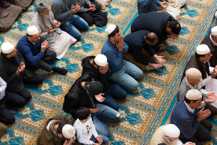 Folk sitter på rekker og det er fullt i det store rommet i moskeen. Foto: Morten Lauveng Jørgensen