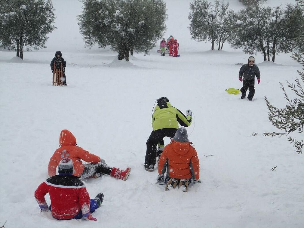 Barn leker ute om vinteren.