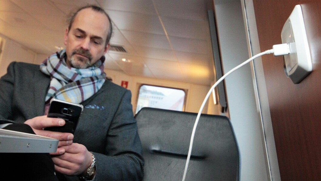 Johannes Larsen, prosjektansvarlig i Ruter, lader mobilen på Nesodden-båten. Foto: Øystein Dahl Johansen/Ruter