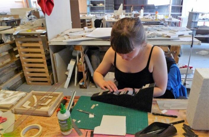 Arkitekt AinaSandTelhaug arbeider med modell. Foto: Privat