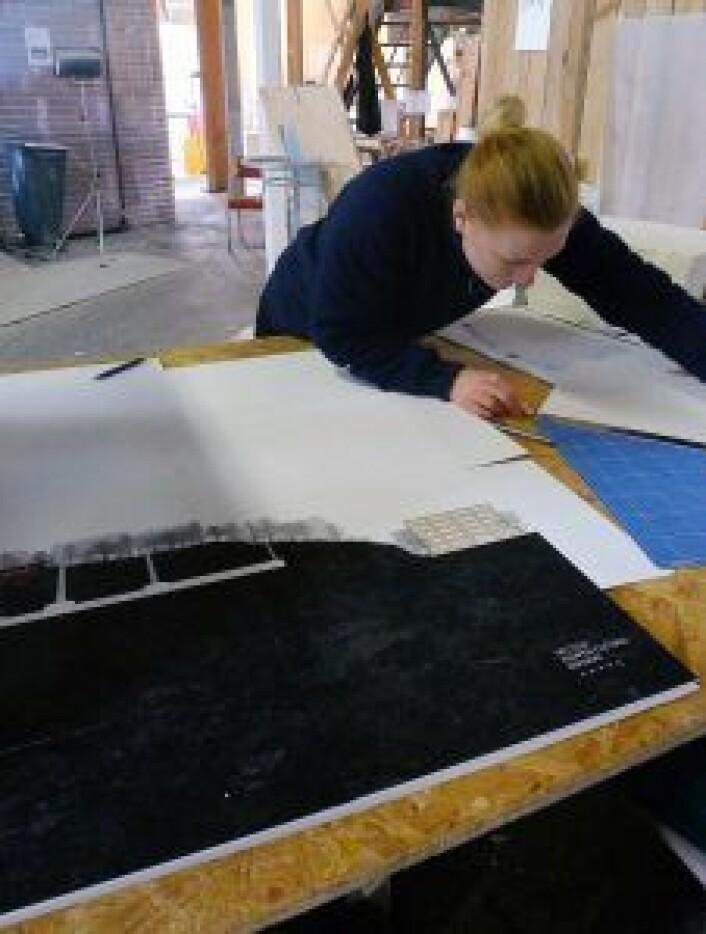Ann-Sofie Indgul arbeider med snitt. På benken ligger en illustrasjon av hvor Kampen kulturbryggeri ligger i terrenget, og hvordan lyssjakter er tenkt plassert. Foto: Telhaug og Indgul
