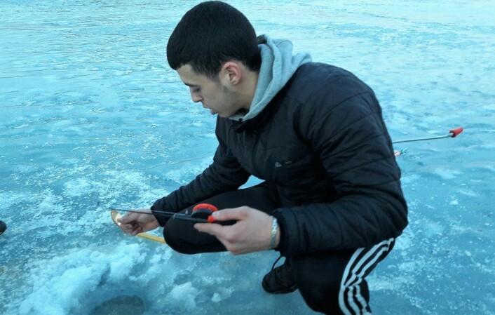 Fiskeekspert Abdesamad El-Amiri (18), Abdi,fra Urban anglers frister fisken med spyfluelarver under en tur på Nøklevann tidligere i år. Foto: Anders Høilund