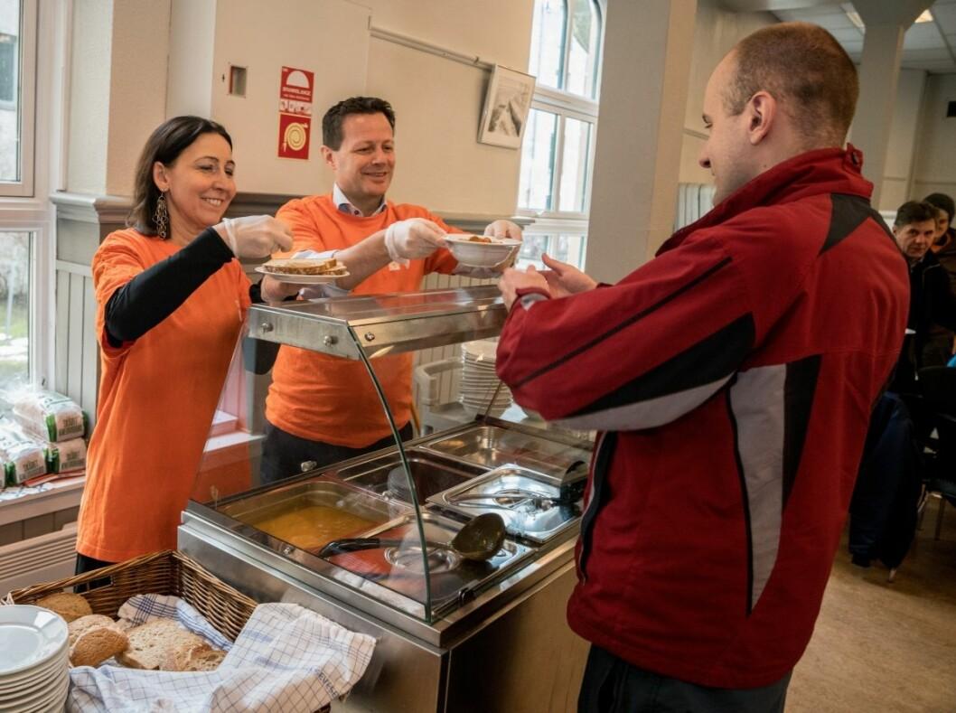 En av gjestene på ByFrokost får servert mat av generalsekretær Adelheid Firing Hvambsal i Kirkens bymisjon og Runar Hollevik, administrerende direktør i Norgesgruppen. Foto: Torstein Ihle