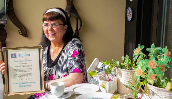 Jeg har vært interessert i spådom siden begynnelsen av 80-tallet, forteller Inger-Marie Lilleengen og viser fram diplomet hun fikk for sin utdannelse innen holistisk healing. Foto: Susanne Skaug