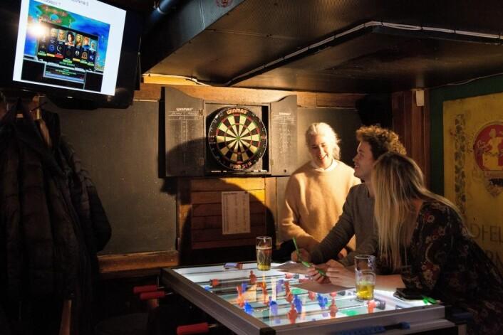 Det er latter rundt bordene og øl i glassene. Quiz-lagene gir inntrykk av å føle seg hjemme. Foto: Ka Man Mak