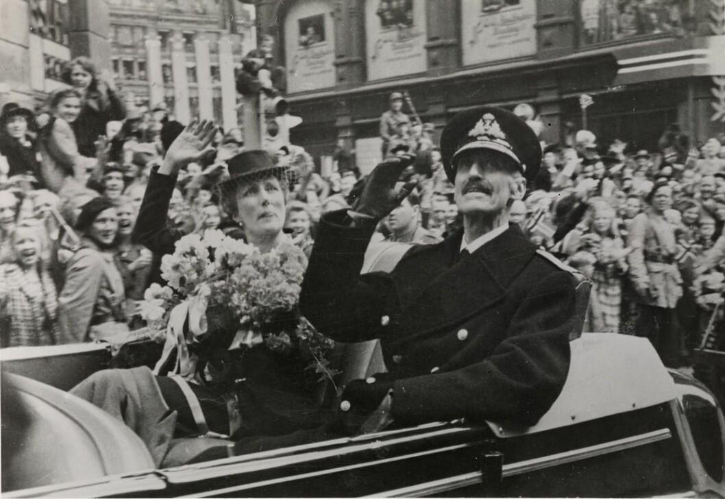 Kong Haralds bestefar Kong Haakon, og kronprinsesse Märtha, i bilkortesje opp Karl Johans gate 7. juni 1945, med feiring av frigjøring og fred etter krigen. Foto: Oslo Museum