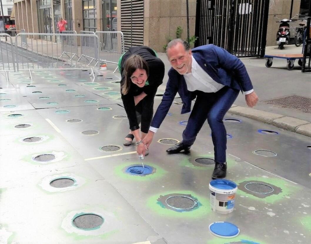 I Øvre Slottsgate var arbeidere i ferd med å legge til gatekunst når svenskene kom på besøk. Partikollegaene Hanna Marcussen (MDG) og Daniel Helldén (Miljöpartiet) ville male i grønt, men den fargen var ikke å oppdrive. Dermed ble det en blå prikk i stedet. Foto: Anders Høilund