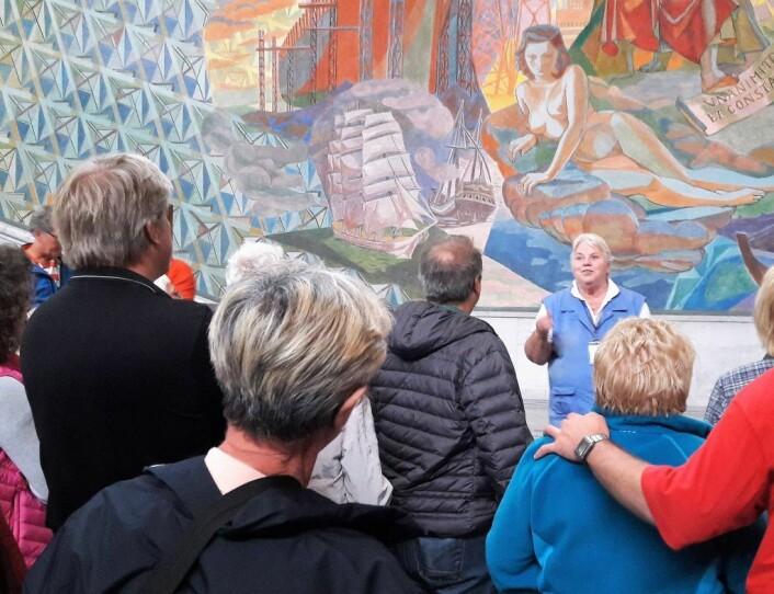 Guide fra Oslo guidebureau foreleser om St. Hallvard i Oslo rådhus. Illustrasjonsfoto