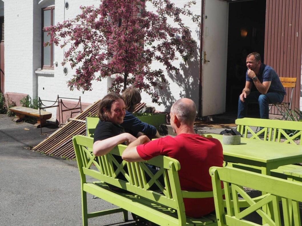 Noen av brukerne hos Prindsen koser seg i solsteika utenfor aktivitetshuset. Foto: Helene Kjeldsberg