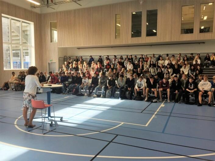 Forventningsfulle elever hører på rektor tale i flerbrukshallen på deres nye skole. Foto: Vegard Velle