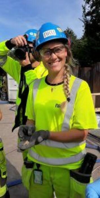 Arkeolog Solveig Thorkildsen viser fram blyseglet hun fant, på størrelse med en halv fyrstikkeske. Foto: Anders Høilund