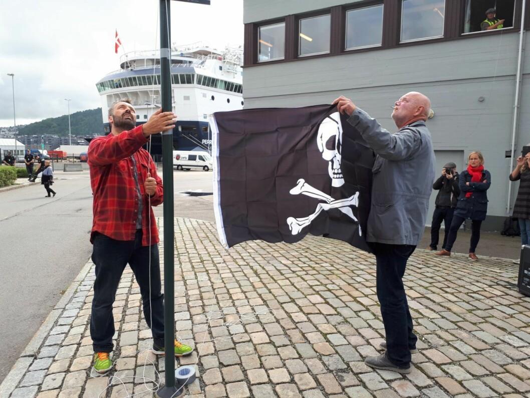 1. september heiste havnearbeider Rune Berre (t.v) og leder i Norsk Transportarbeiderforbund, Lars M. Johnsen, piratflagget over Oslo havn. Mandag ble det klart at havna blir  såkalt bekvemmelighetshavn. Foto: Christian Boger