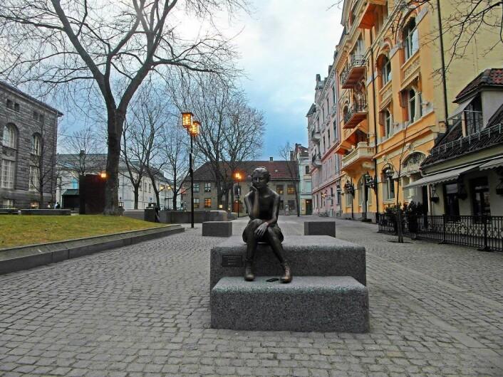 Sittende pike med hodetelefoner, av Marit Krogh. Statue på Bankplassen som hindrer fremkommeligheten på en trivelig måte. Foto: Cafe Engebret