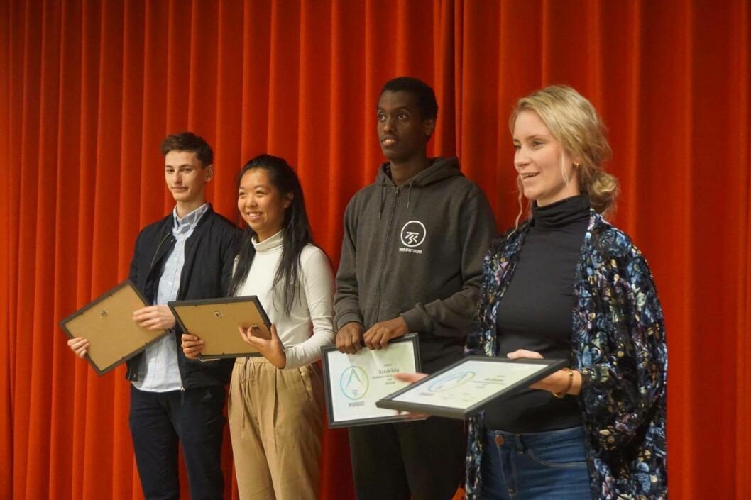 Ungdommene får diplom. Fra venstre: Talha Yesil, Rose Lu, Sharmarke Kahiye, og Line Oma, leder av bydelsutvalget. Foto: Sindre Andresen