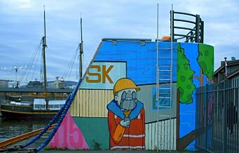På havna fins en grå betongkloss lyst opp med en fargerik havnearbeider