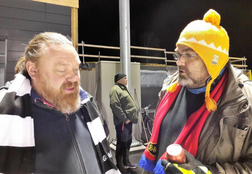 Dette er bandy, og supporterne er snille med hverandre. Sagenes Truls Westlie og Skeids Morten A Fagerli diskuterer kampen over en Nordmarka vørterøl. Foto: Anders Høilund