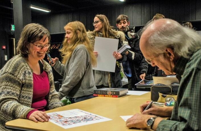 Don Rosa signerer og skriver en liten hilsen til Ingeborg Marie Ekenes, mens andre fans venter med på å få signert bøker og plakater. Foto: Morten Lauveng Jørgensen