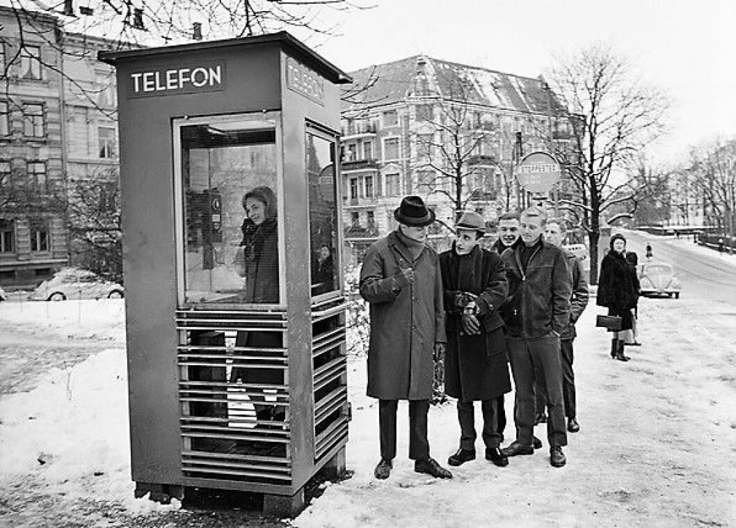 """Johnny Bergh (med hatt), Nandor Hamza (viser klokken) og Stein Roger Bull (hendene i bukselommen), i omtrent 1965. Fotografert i forbindelse med fjernsynsproduksjonen """"Kunden har alltid rett"""". Foto: HENRIK ØRSTED / OSLO MUSEUM / CC BY-SA"""