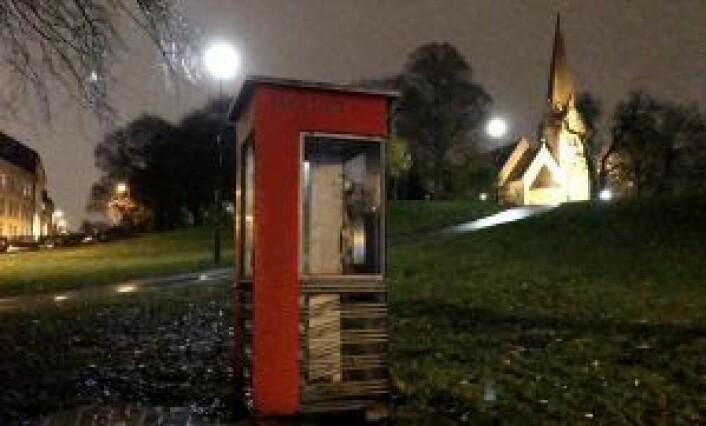 Her er en av de 19 røde telefonkioskene som er igjen i Oslo. Den står på Vålerenga, med Vålerenga kirke i bakgrunnen. Foto: Elin Barosen