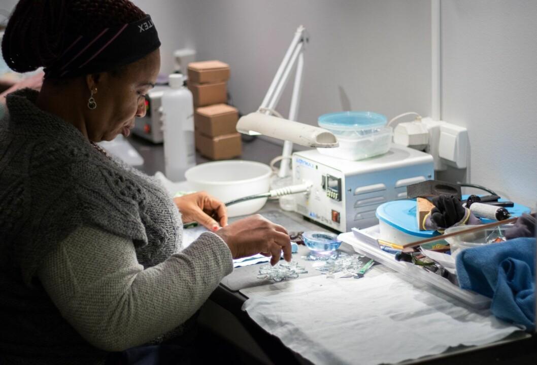 Små, nøyaktig tillagde glassbiter skal settes sammen til en liten engel. Konsentrasjon er viktig sier Ugbo. Foto: Kyrre Songstad Seim