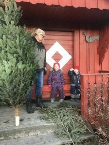 Ole-Petter foran stabburet på familiegården med barnebarna Nora og Oscar. Foto: Privat