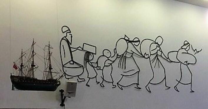 """Veggdekorasjon i Tonsen kirke som symboliserer viktigheten av å bære livets byrder sammen. Skipet du ser bakerst henger i realiteten ned fra kirketaket midt i kirken. Ulike skipsmodeller finnes i mange norske kirker. De kalles """"votivskip"""" og symboliserer kirkelydens ferd mot evigheten. Foto: Kjersti Opstad"""